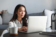 Young ambitious asian girl working remote from home, looking at laptop screen and smiling. Woman checking mail or researching while telecommuting, sitting on floor at her apartment