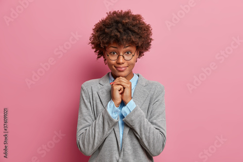 Isolated shot of dark skinned pretty woman in eyeglasses with curly hairstyle keeps hands under chin, listens attentively interlocutor, prepares for formal meeting, isolated on pink background Wallpaper Mural