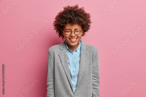 Obraz na plátně Overjoyed entrepreneur rejoices over successful deal, laughs out loudly, closes eyes, wears formal grey jacket, expresses positive emotions, isolated on pink background