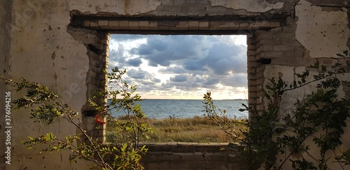 View of the sea in cloudy day through the wall of the destroyed building Fototapet