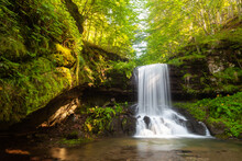 Amazing Sunrays On Scenic Skok Waterfall, Long Exposure Blurred Motion Of The Water And Vivid Green Plants On The Wet, Dark Rocks