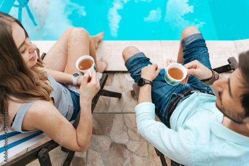 Obraz Lovely young couple spend time together at home near the pool while chatting and enjoying tea - fototapety do salonu