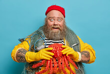 Image Of Happy Positive Lobsterman Glad To Catch Big Octopus, Enjoys Fishing At Sea, Has Lucky Day, Wears Red Hat, Yellow Gloves, Poses Over Blue Background. Bearded Sailor Has Marine Travel