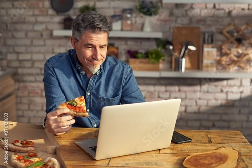 Fototapeta Man working from home on laptop computer, sitting at table in kitchen, eating online ordered pizza