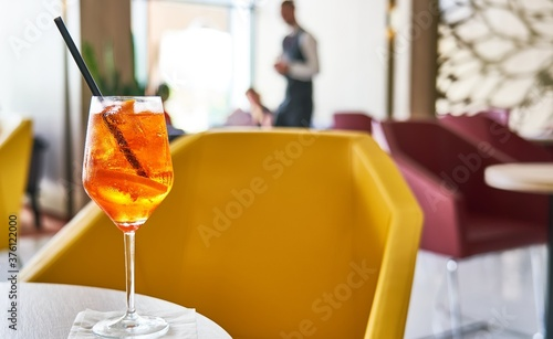 Glass of cold refreshing aperol spritz cocktail on table in summer Fototapeta