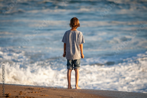 Boy standing on sand looking out at rough water Canvas Print