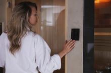 Woman Choosing Infrared Sauna Temperature. Home Spa Concept