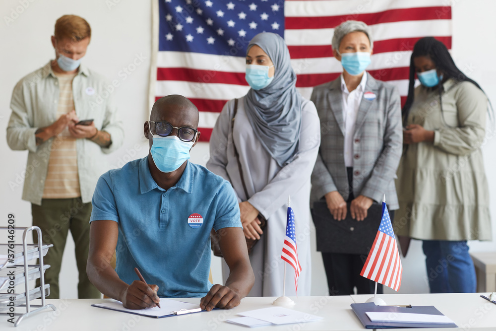 Leinwandbild Motiv - Seventyfour : Multi-ethnic group of people standing in row and wearing masks at polling station on election day, focus on African-American man registering for voting