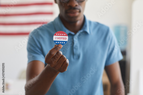 Cropped portrait of modern African man holding I VOTED sticker, copy space