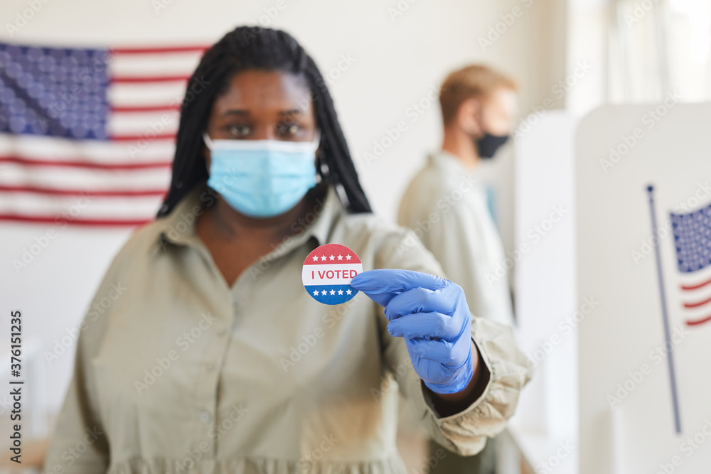 Leinwandbild Motiv - Seventyfour : Blurred portrait of African-American woman holding I VOTED sticker while standing t polling station on post-pandemic election day, copy space