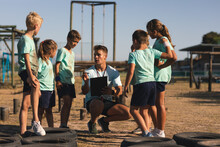 Male Fitness Coach Instructing Kids At A Boot Camp