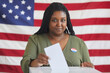 Leinwandbild Motiv Portrait of young African-American woman putting vote bulletin in ballot box and looking at camera while standing against American flag on election day, copy space
