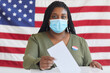 Leinwandbild Motiv Portrait of young African-American woman wearing mask putting vote bulletin in ballot box and looking at camera while standing against American flag on election day, copy space