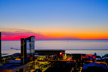 Sunset View Over Lake Erie With Cleveland Cityscape Covered In Pink, Purple And Orange Shades With Illuminated Streets And Buildings
