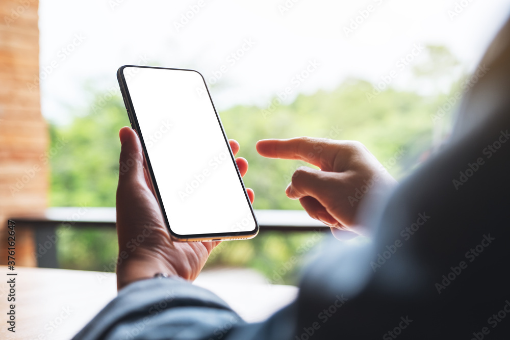 Fototapeta Mockup image of a woman holding and pointing finger at mobile phone with blank white desktop screen