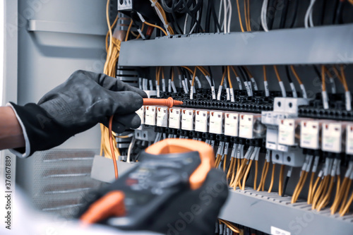 Electrical engineer using digital multi-meter is measuring equipment to checking electric current voltage at circuit breaker and cable wiring system in main power distribution board Canvas Print