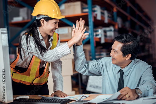 Cuadros en Lienzo Engineer woman and businessman wearing a hardhat standing cargo at goods or merchandise warehouse and check control loading from Cargo freight ship for import and export