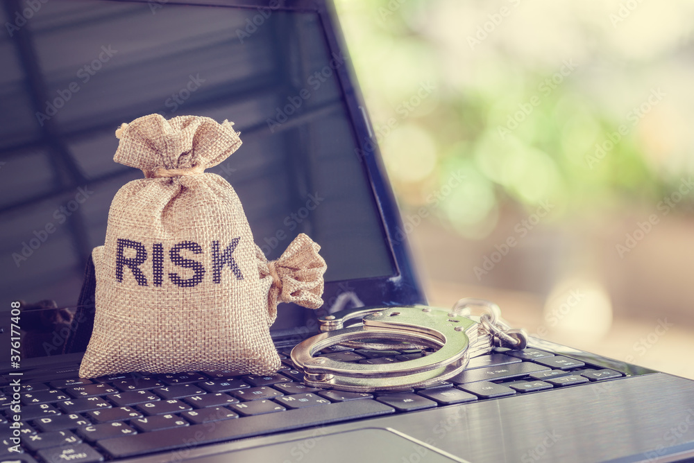 Fototapeta Cybersecurity risk and threat, information technology concept : Bag with a word RISK and a handcuff on a laptop computer, depicts protecting integrity, confidentiality, personal data and digital asset