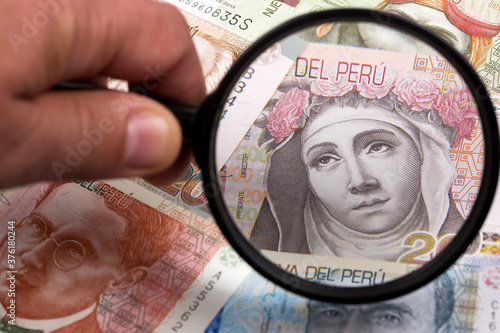 Fotografering Peruvian money in a magnifying glass a business background