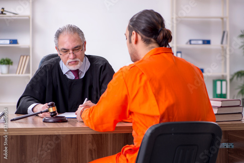 Old male judge meeting with young captive in courthouse Fototapet