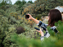 A Young Girl With Dark Hair, Wearing Glasses, Takes Photos Of Nature On Her Smartphone. The Smartphone Is Charged From The Power Bank. The Concept Of Modern Hiking. A Keepsake Photo From The Trip
