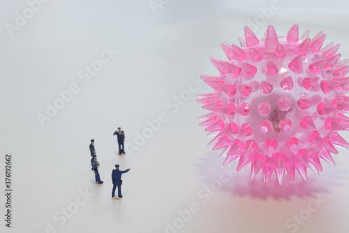 Fototapeta 巨大なコロナウイルスを監視する警察官のミニチュア人形
