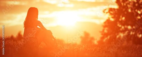 Fotografie, Obraz Silhouette of a woman sitting on a field.