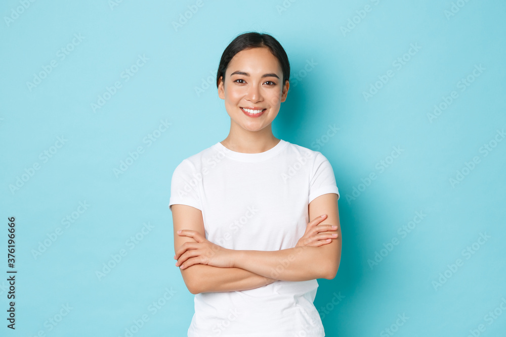 Fototapeta Portrait of confident asian girl smiling pleased, cross arms chest confident pose, female student looking upbeat and determined standing blue background, casual clothes, lifestyle concept