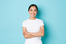 Portrait Of Confident Asian Girl Smiling Pleased, Cross Arms Chest Confident Pose, Female Student Looking Upbeat And Determined Standing Blue Background, Casual Clothes, Lifestyle Concept