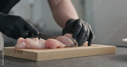 Man hands in black gloves cutting chicken fillet on oak board Poster Mural XXL