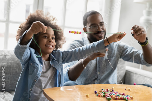 Stampa su Tela Happy small african american kid girl involved in handmade activity with affectionate smiling biracial father at home, enjoying making wooden bracelets accessories at home, sitting at coffee table