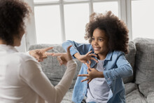Smiling Little African American Girl With Hearing Loss Practicing Body Language With Professional Female Therapist At Home, Happy Deaf Kid Communicating Nonverbal With Mum Using Signs And Gestures.
