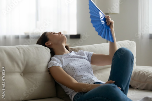 Foto Exhausted young woman waving paper fan, suffering from high indoors temperature