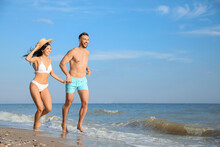 Happy Young Couple Running Together On Beach