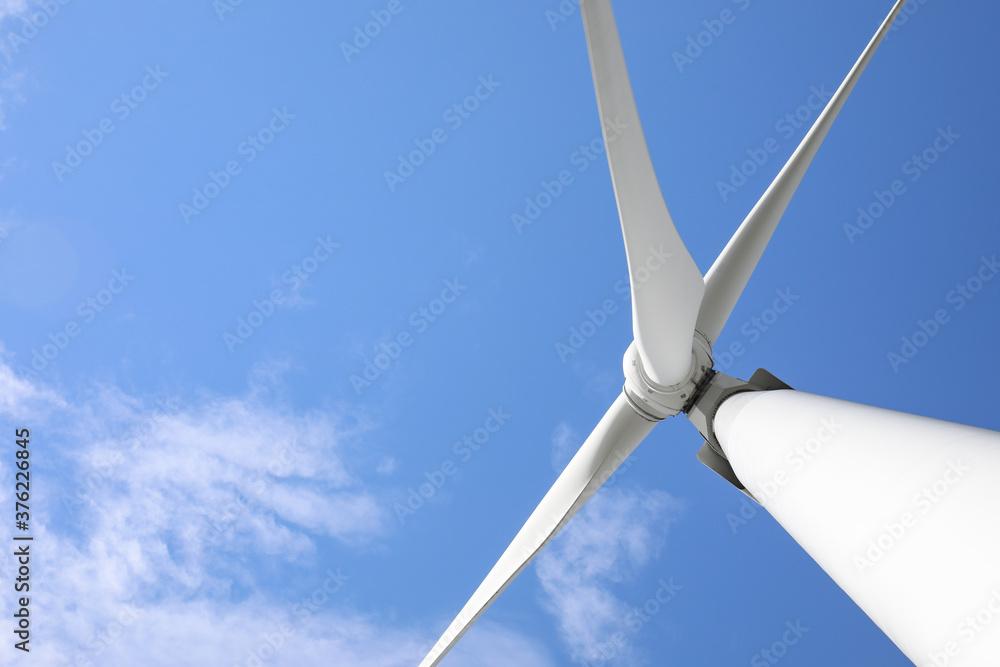 Fototapeta Wind turbine against beautiful blue sky, low angle view. Alternative energy source