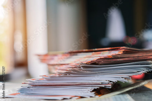 Business Brochure in Documents concept : Businessman hands working in stacks brochures paper files for checking document achieves reports on busy work desk office