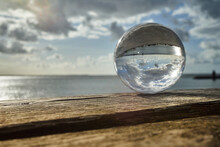 View Through A Crystal Ball On An Old Extended Wooden Bench Over The Sea With The Mudflats And The Sky With Clouds