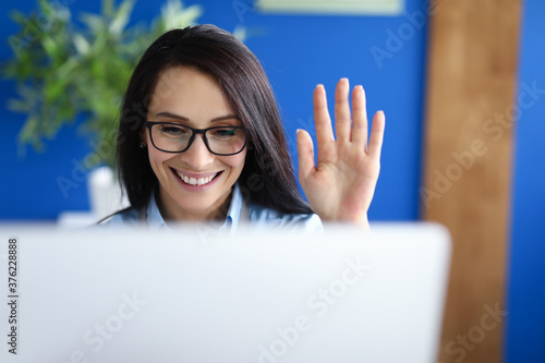 Photo Businesswoman sits at computer and prevails over interlocutor with her hand