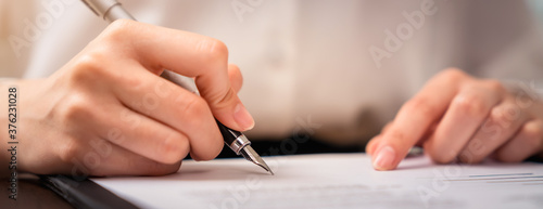 Businessman signing financial contract and hand holding pen putting signature after reaching an agreement.