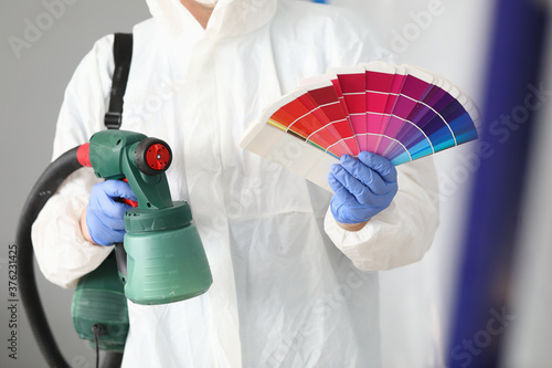 Master holds spray gun and color palette in crayfish Fototapet