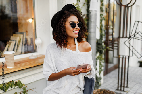 Fotografie, Obraz Young mixed woman with afro hairstyle talking by mobile phone and  smiling in urban background