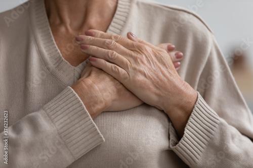 Fotografía Close up cropped image hopeful grateful mature senior woman keeping hands on che