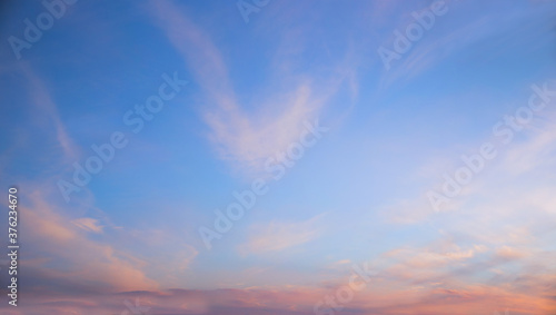 Foto blue sky and fluffy pink clouds at sunset, horizontal format