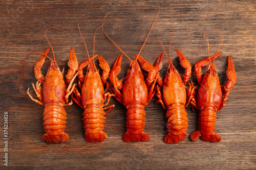 Photo Delicious boiled crayfishes on wooden table, flat lay