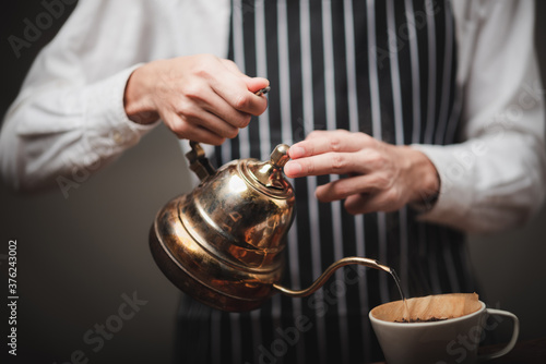 barista pouring hot water from the kettle over the coffee powder to extract making the freshly brewed coffee in the coffee cafe Canvas Print