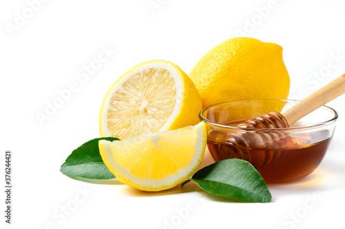 Fototapeta Fresh lemon with leaf and honey with honey dipper isolated on white