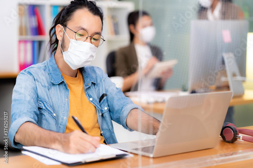 Fototapeta Asian businessman working in new normal and social distance office obraz