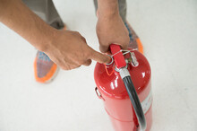 Close Up Man Showing How To Use A Fire Extinguisher On A Training Fire For Employees Industry.