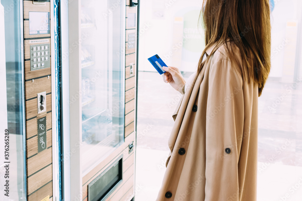 Fototapeta woman uses her credit card to pay at the vending machine