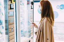 Woman With A Face Mask Uses Her Credit Card To Pay At The Vending Machine